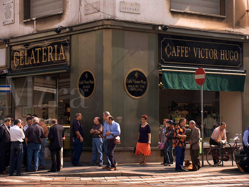 Men gather for Sunday morning conversation in front of Cafe Victor Hugo on Via Speronari in Milan Ital