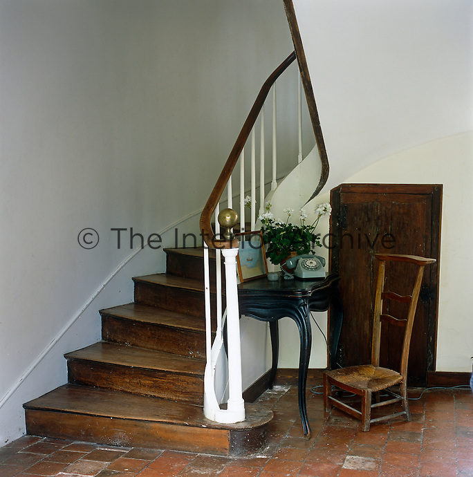 The hallway of the 17th century French manor house has a curved staircase and an antique telephone table