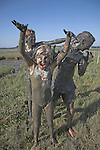 Children covered from head to toe in mud playing in pools of the Butley Creek river estuary, Suffolk, England, UK no MR
