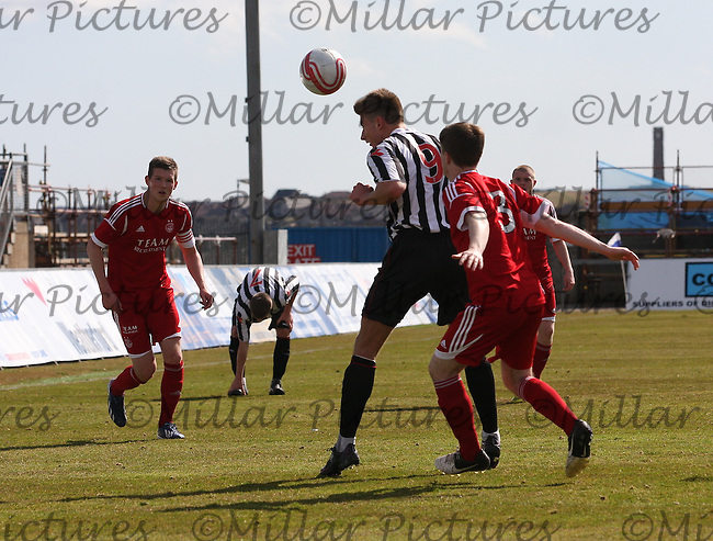 Michael Fulton heads under pressure from Craig Duguid in the Aberdeen v St Mirren Clydesdale Bank Scottish Premier League Under 20 match played at Balmoor Stadium, Peterhead on 19.4.13.