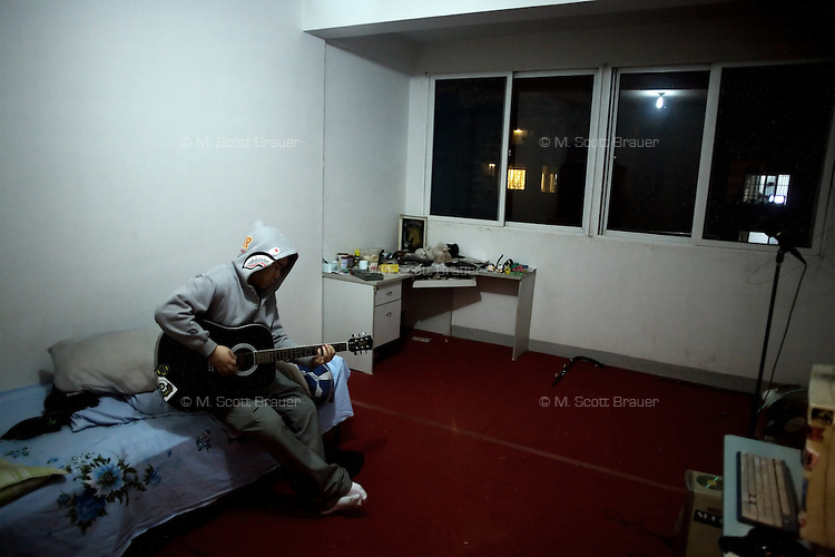 Jobby, guitarist and drummer for the Chinese punk band Overdose, practices guitar in a bedroom in an apartment in the northern outskirts of Nanjing, China.