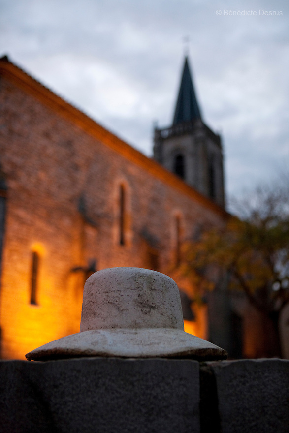 9 december 2009 - Coustilleres' hat factory, Septfonds, France - Cement hat in the town of Septfonds. On the background, the church..Septfonds is the heart of French straw hat making, due to its very ancient hatter tradition. The hat making industry had its commercial peak in the late 19th century..Coustillères is a family owned hat making factory that has been making straw hats in Septfonds for nearly 100 years. They make hats from straw, felt, and cloth as well as caps. The current owner is Jean-Claude Coustilleres. He is one of the last hat makers of the region..The straw hat making process is very labor intensive and numerous hands are involved. Nearly all of the equipment is over 100 years old, they use the original presses and tools including aluminium molds and sewing machines and dye their own straw continuing the traditional methods of manufacturing. The hat blocking and shaping, straw braids construction and dyeing are all done by hand..The company works on behalf of fashion houses and makes a variety of regional and historical hats. It produces 2 collections a year distributed by a network of salespeople and through a catalog to clients around the world. Photo credit: Benedicte Desrus