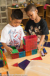 Education Preschool 3-4 year olds classroom scenes two boys building structure from magnetic blocks