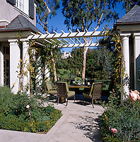 A summer dining table has been set up under an arbour over which wisteria and other climbers are being encourage to grow
