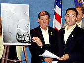 Washington, D.C. - June 29, 2005 --  Anthony Gardner, left, displays what he considers to be objectionable art work during a press conference in Washington, D.C. on June 29, 2005. Mr. Gardner is a member of the Coalition of 9/11 Families who are visiting Washington to lobby against the International Freedom Center (IFC).  Bill Doyle looks on from center.<br /> Credit: Ron Sachs / CNP