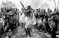 Ethiopia. South Omo Zone. Salamago district. Hana (little village). Bodi tribe. Nomadic. Celebrations. Young man dance with his machine gun, a kalachnikov, among a group of men and women clapping hands and singing. Other young men hold their wood stick (used for the cattle and as a fighting tool).  The Bodi tribe is located in the Debub Omo Zone (South Omo Zone) of the Southern Nations, Nationalities and Peoples's région. © 2001 Didier Ruef