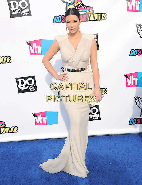 Kim Kardashian.The 2011 Do Something Awards held at The Palladium in Hollywood, California, USA..August 14th, 2011.beige full length white grey gray dress maxi hand on hip black belt gold clutch bag .CAP/RKE/DVS.©DVS/RockinExposures/Capital Pictures.