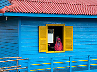 A colourful school building and students on the outskirts of Siem reap near the Tonle Sap Lake, Cambodia