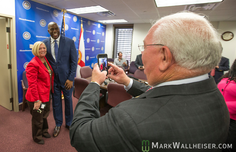 "Florida Senator Bill Montford, right, takes a photo of his assistant Marsha Mathis with  Earvin ""Magic"" Johnson, retired professional basketball player and current president of operations for the Los Angeles Lakers of the NBA, before a meeting with the Florida Senate Democratic Caucus  about health care at the Florida Capitol in Tallahassee Florida March 13, 2017."