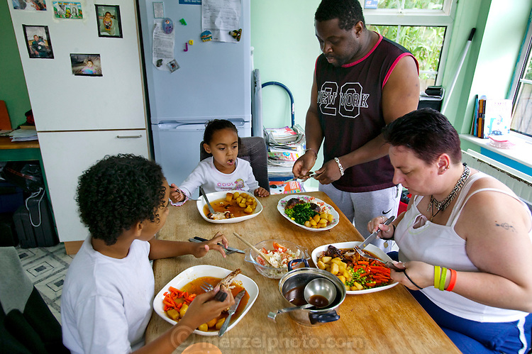 """Jill McTighe (right), a mother and school aide,  enjoys dinner with her husband Earl Gillespie and their children at their home in Willesden, London, United Kingdom. (From the book What I Eat: Around the World in 80 Diets.) The caloric value of her day's worth of food on a """"bingeing"""" day in the month of September was 12300 kcals. The calorie total is not a daily caloric average.  Jill is  31 years old; 5 feet, 5 inches tall;  and 230 pounds. Honest about her food addiction replacing a drug habit, Jill joked about being a chocoholic as she enthusiastically downed a piece of chocolate cake at the end of the photo session. Her weight has yo-yoed over the years and at the time of the picture she was near her heaviest; walking her children to school every day was the sole reason she didn't weigh more. She says this photo experience was a catalyst for beginning a healthier diet for herself and her family. Jill herself is MODEL RELEASED  [Use of Jill McTighe images must be used contextually only and use cleared with Peter Menzel Photography on a case by case basis.]"""