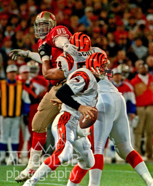 San Francisco 49ers vs. Cincinnati Bengals at Candlestick Park Sunday, December 5, 1993.  49ers beat Bengals 21-8.  Cincinnati Bengals tackle Tom Scott (74) hold off San Francisco 49ers defensive end Artie Smith (95) for quarterback David Klingler (7). .