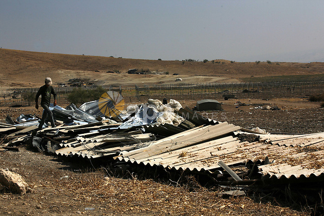 A Palestinian walks on the remains of his tent destroyed by the Israeli army, in the West Bank village of Faresiya near Tubas, Monday, July 19, 2010. Israeli forces demolished a cluster of tents and shacks belonging to Palestinians in the northern West Bank . Photo by Wagdi Eshtayah