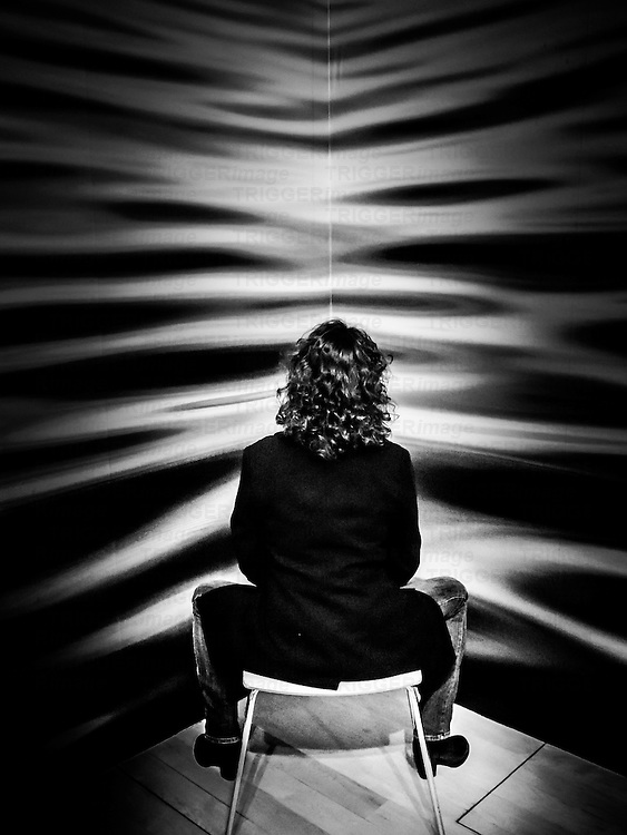 Daylight interior shot rear view of a seated dark curly haired woman.