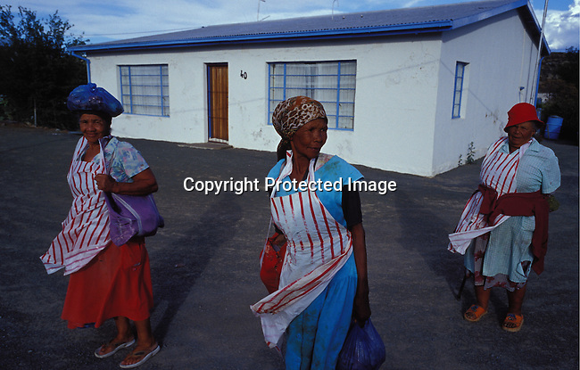 dipprur00033. People Rural Living. Sutherland. Three of the local women returning from shopping. They are wearing scarves and aprons. One woman is balancing a parcel on her head. House in backround. .©Per-Anders Pettersson/iAfrika Photos.