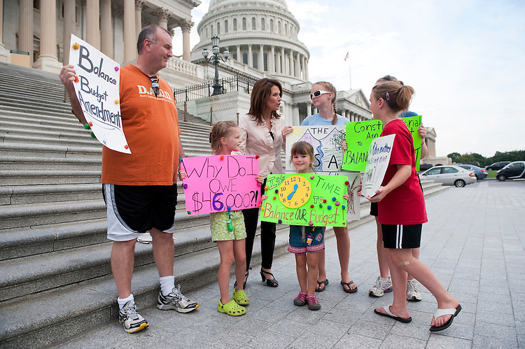 UNITED STATES - AUGUST 1: Presidential candidate Rep. Michele Bachmann, R-Minn., poses for a photo with the Matthews family from Kansas City, Mo., as they hold a family protest calling for a balanced budget at the House steps during the vote on the debt ceiling bill in the House of Representatives on Monday, Aug. 1, 2011. (Photo By Bill Clark/Roll Call)