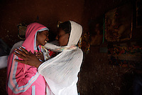 Emembet Albachew, 26 years old, on left, HIV positive, breaks in tears of joy and gratitude with Asnagetch, the woman that took care of her daughter during a full month hospitalization in Addis Ababa, Ethiopia on Tuesday July 18 2006. Emembet lives with her daughter, 3 years old Magdass, her only reason to live. On June 20th she was reported to be dead by the St Paul hospital staff while she was enduring a deep physical crises. after almost 4 weeks of hospitalization she was discharged and could finally reunite with her daughter that meanwhile lived with a local home base care giver. . Ethiopia is one of the countries most affected by HIV/AIDS. Of its population of 77 million, three million are HIV-positive, according to government statistics. Every day sees 1,000 new infections. A million children under 14 have lost one or both parents to AIDS, and 200,000 children are living with AIDS. That makes Ethiopia the country with the most HIV-positive children.