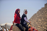 Egyptian girls ride camels in front of the Giza pyramids, on the third day of Eid al-Fitr holiday which marks the end of the Muslim holy month of Ramadan, in Cairo June 27, 2017. Photo by Amr Sayed
