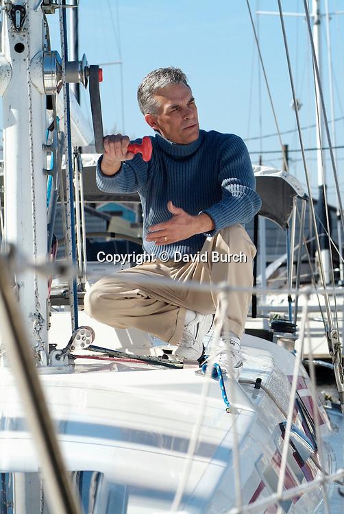 Man working rigging on sailboat in marina