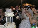 Armenia 2007 <br /> A Yezidi wedding: the newlyweds sharing  the wedding cake <br /> Armenie 2007 <br /> Un mariage Yezidi dans un village: les jeunes maries mangeant du gateau de mariage entour&eacute;s de leurs invites.