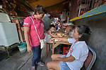 Deaconess Irene Lagahit Vioya talks with a woman on a narrow street in a poor neighborhood in Manila, Philippines. A graduate of Harris Memorial College, she works on the staff of Knox United Methodist Church.