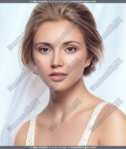 Beautiful young woman tranquil exotic face with clean natural makeup and light brown hair on light flowy fabric background