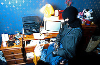 Burglar wearing a balaclava and gloves so as he cannot be identified or traced through his fingerprints has broken into a house and is ransacking through all the drawers for items to steal. This image may only be used to portray the subject in a positive manner..©shoutpictures.com..john@shoutpictures.com