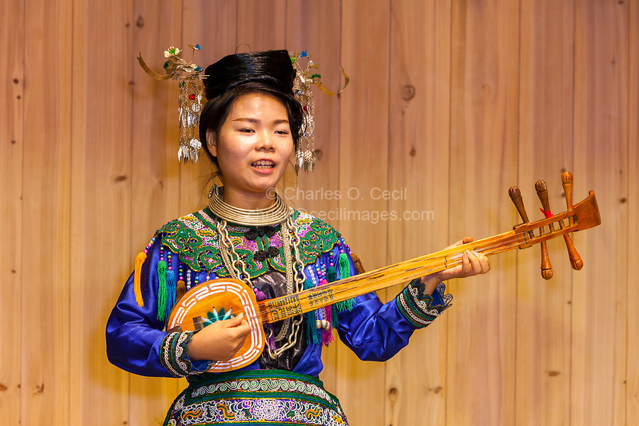 Zhaoxing, Guizhou, China.  Young Woman of the Dong Ethnic Minority Playing a Five-stringed Lute (pipa).