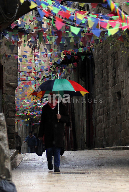 A Palestinian man walks with his umbrella under the rain, during a winter storm, in the West Bank city of Nablus, on December 18, 2016. Photo by Nedal Eshtayah