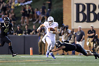 WINSTON-SALEM, NC - SEPTEMBER 13: Sam Howell #7 of the University of North Carolina avoids a tackle by Luke Masterson #12 of Wake Forest University during a game between University of North Carolina and Wake Forest University at BB