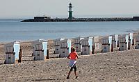 23rd April 2020, Mecklenburg-Vorpommern, Warnemünde: A single woman jogs along the strand during the covid-19 pandemic