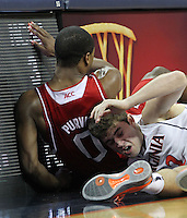 Virginia guard Joe Harris (12) goes after the loose ball with North Carolina State guard Rodney Purvis (0) during the game Saturday in Charlottesville, VA. Virginia defeated NC State 58-55.