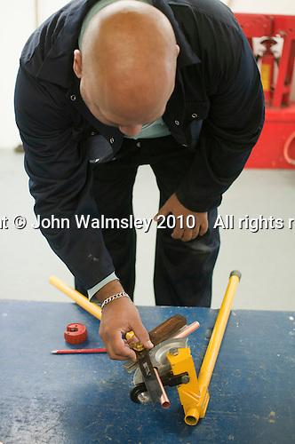 Plumbing student using a pipe bender, Able Skills, Dartford, Kent.