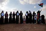 Women of the Kamushi family stand with the portraits of four male family members whose bodies were found in mass graves, during the burial of eight bodies found last week in a mass grave near the town of Al-Qala in the Nefusa Moutains, Libya, Friday, Sept. 30, 2011. The eight were reburied next to 35 bodies found in a separate mass grave in the area. Members of the Amazigh indigenous tribe, the men were arrested from their homes and at checkpoints by pro-Gaddafi forces, imprisoned, and finally executed sometime in June. The men, many of them related as fathers and sons, or as brothers, were missing until the first, larger mass grave was found in mid-August.