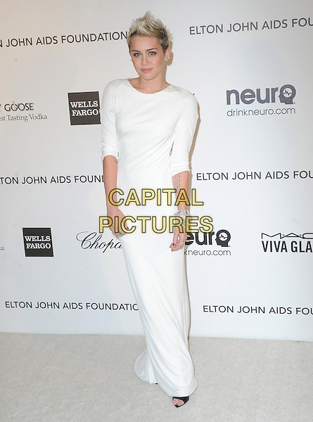 Miley Cyrus (wearing Azzaro).The 21st Annual Elton John AIDS Foundation Academy Awards Viewing Party held at The City of West Hollywood Park in West Hollywood, California, USA..February 24th, 2013.oscars full length dress white long sleeves diamond bracelets .CAP/DVS.©DVS/Capital Pictures.