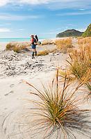 Female tramper on Three Mile Beach near Okarito, Westland Tai Poutini National Park, West Coast, UNESCO World Heritage Area, New Zealand, NZ