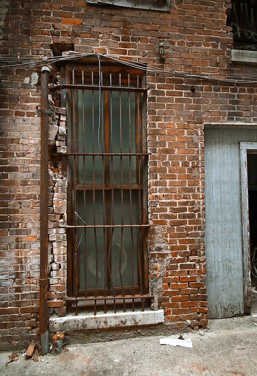 Broken brick wall with metal guard over window