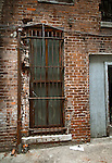 Broken brick wall with metal guard over window