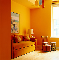 The guest room of a New York apartment is suffused with a welcoming orange glow from the painted walls and upholstery