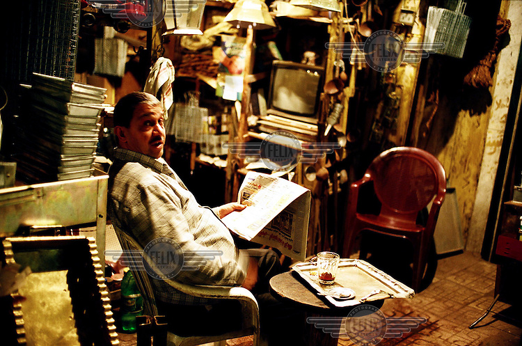 A seller of old bric-a-brac and books reads a newspaper in his shop in Khan Al-Khalili, also known as Islamic Cairo. Although the district is a popular destination for visiting tourists it is actually overpopulated and suffers from poor sanitation services..