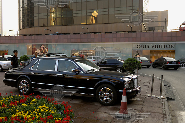 Conspicuous wealth - a privately-owned Bentley car parked by a luxury shopping mall near a Louis Vuitton shop window.