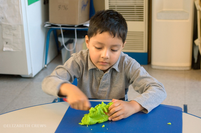 Berkeley CA  Preschool boy constructing with play-do, working individually in class.