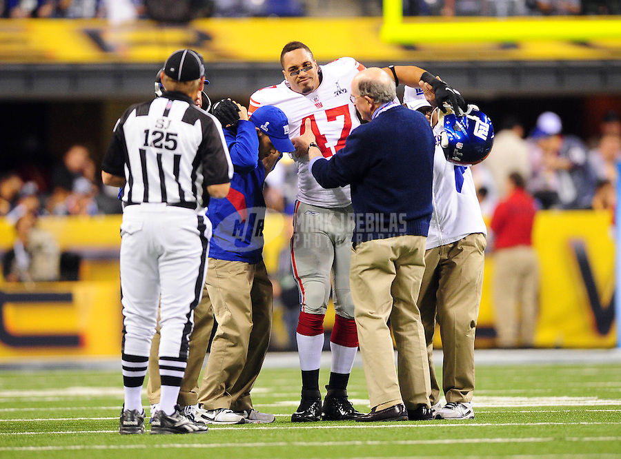 Feb 5, 2012; Indianapolis, IN, USA; New York Giants tight end Travis Beckum (47) is assisted off the field after an injury during the first half of Super Bowl XLVI against the New England Patriots at Lucas Oil Stadium.  Mandatory Credit: Mark J. Rebilas-