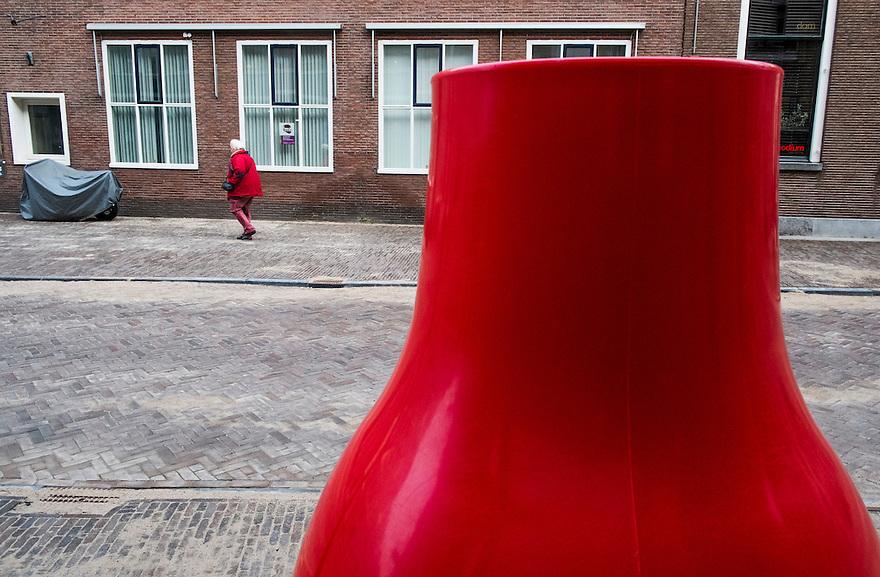 Nederland, Utrecht, 23 feb 2014<br /> Rode vaas staat op straat bij een winkel. Aan de overkant loopt iemand in het rood. <br /> <br /> Foto(c): Michiel Wijnbergh