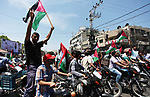 Palestinians ride motorcycles and carry the Palestinian flag during a demonstration organized by the National Authority for Return and Breaking the Siege in Gaza City, June 5, 2018. Photo by Mahmoud Ajour