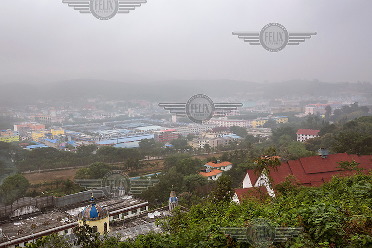 A view of Mong La amidst the morning mist. <br /> The town of Mong La on the Burma - China border in western Burma (Myanmar) is technically in Burma but relies on most infrastructure - electricity, telecommunications - on neighbouring China. The main currency used here is the Chinese yuan. The town is in the middle of the so-called &quot;Golden Triangle&quot; and specialises in gambling and the sale of poached and endangered species. Tiger skins, rhino horns, pangolins and other creatures are freely traded here and many are available to eat. Prostitution is rife and just outside the town a bear farm keeps between 500 and 600 bears which are kept in captivity for their bile which is harvested for medicinal use.