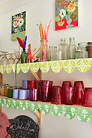 In the kitchen, coloured glassware and china is displayed on shelves trimmed with patterned fabric.