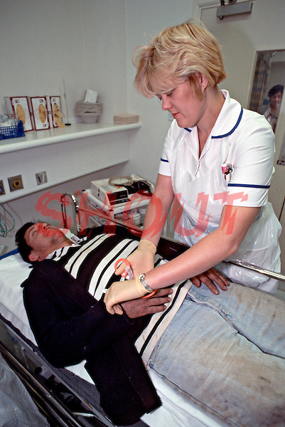 A vagrant being attended to in the crash room of an A&E department in a hospital. The nurse is cutting off his coat so as to be able to assess his injuries and his condition. This image may only be used to portray the subject in a positive manner..©shoutpictures.com..john@shoutpictures.com