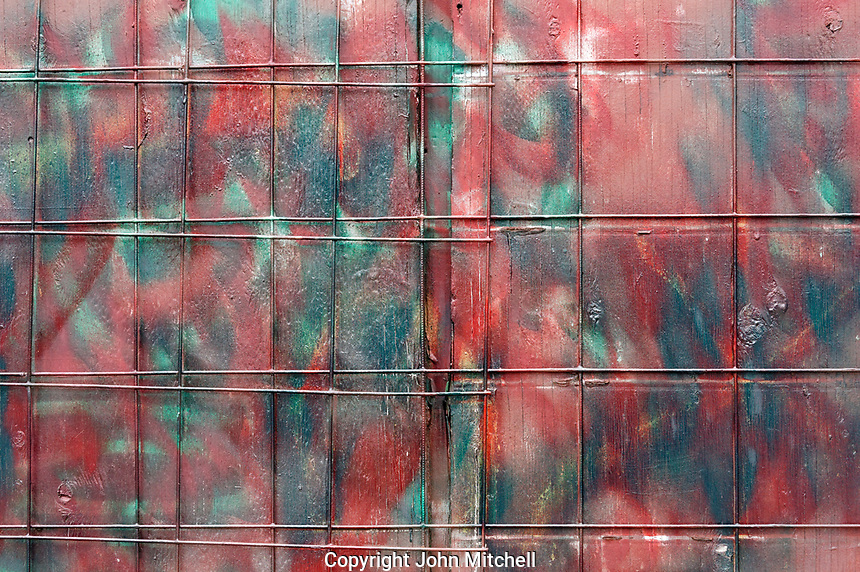 Colorful abstract design painted on a weathered wooden wall of a building