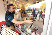 NWA Democrat-Gazette/FLIP PUTTHOFF <br />CLEAR AS GLASS<br />Sayer Canova cleans windows Tuesday Nov. 6 2018 in downtown Bentonville as pedestrians are reflected in the glass. Canova was washing windows at the Walmart Museum on the town square.
