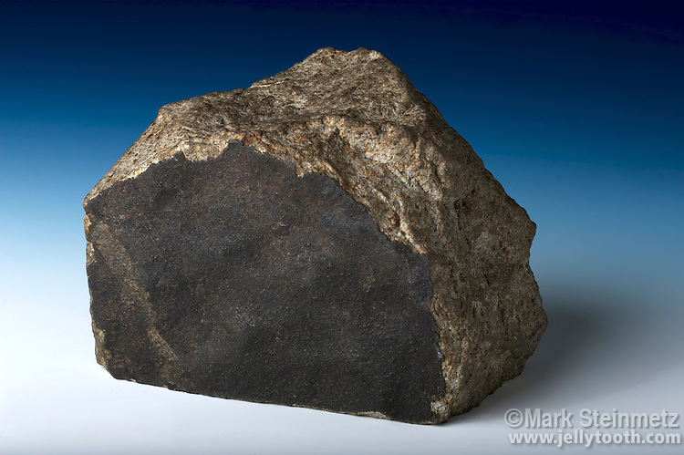 Fusion crust visible on a stony meteorite, a fragment of the New Concord meteorite, a shower of stones which was observed falling around the town of New Concord, Muskingum County, Ohio, mid-day, May 1, 1860. A fusion crust is a dark and glassy crust formed by high temperatures melting the surface of the meteorite during entry into the atmosphere.